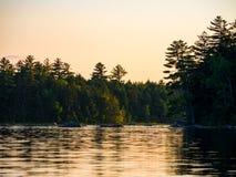 Orilla del lago mountain, Forest Glowing en la puesta del sol imagenes de archivo