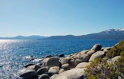 Orilla del lago Tahoe con las piedras y las montañas de la nieve Fotos de archivo libres de regalías