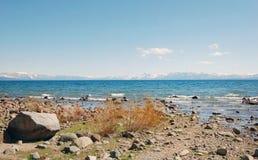 Orilla del lago Tahoe con las rocas y las montañas de la nieve Foto de archivo libre de regalías