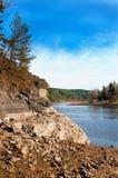 Orilla del río escarpada y rocosa con el río y la madera Imágenes de archivo libres de regalías