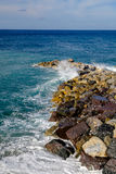 Orilla rocosa con las ondas cristalinas, Liguria, Italia del puerto deportivo de Deiva Imagen de archivo libre de regalías