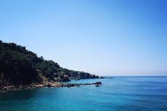 Orilla rocosa Costa meridional de Turquía Mar azul tranquilo y cielo claro Imagen de archivo libre de regalías