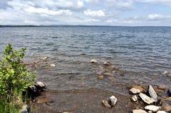 Orilla rocosa del lago, en la distancia usted puede ver las montañas de Ural Foto de archivo libre de regalías