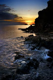 Orilla rocosa del océano y de la puesta del sol Fotos de archivo