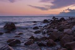 Orilla rocosa durante una puesta del sol hermosa sobre el mar Fotografía de archivo