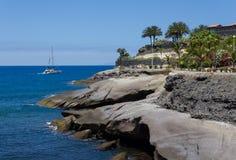 Orilla y barco rocosos del océano Fotos de archivo