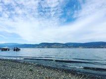 Orilla y playa del lago con el barco en muelle Fotografía de archivo