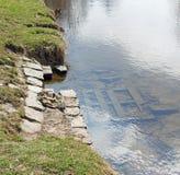 Orilla y tablones de madera en el cauce del río Foto de archivo