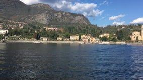 Orillas del lago Como con la ciudad y las montañas italianas en fondo metrajes