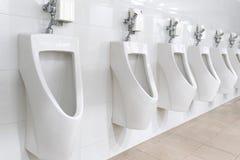 Orinal blanco en cuarto de baño del ` s de los hombres Foto de archivo libre de regalías