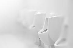 Orinales en el retrete público o el lavabo blanco, diseño interior, mal Fotografía de archivo libre de regalías