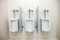 Orinales en los cuartos de baño de los hombres. Fotos de archivo