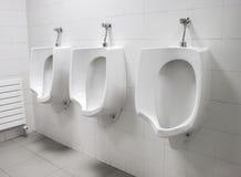 Orinali bianchi sulla parete alla toilette pubblica Immagini Stock Libere da Diritti