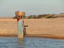 Orissa woman crosses tidal waters Stock Photo