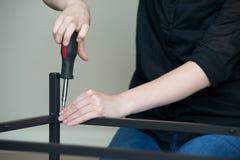 Orizzontale delle mani che avvitano insieme mobili metallici, sinistra ad angolo immagini stock libere da diritti