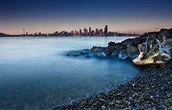 Orizzonte della città da una spiaggia rocciosa Fotografia Stock