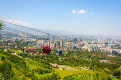 Orizzonte di Almaty con la cabina di funivia Fotografia Stock