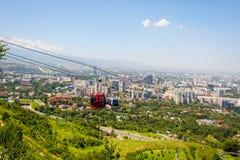 Orizzonte di Almaty con la cabina di funivia Fotografie Stock Libere da Diritti