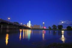 Orizzonte di Dallas del centro alla notte con le riflessioni nel fiume Trinity sommerso immagini stock