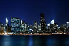 Orizzonte di Manhattan alle notti Immagini Stock Libere da Diritti