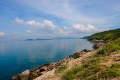 Orizzonte di mare con le scogliere rocciose della riva ed il fondo blu-chiaro del cielo del sole Onde del mare che si schiantano  Fotografia Stock