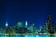 Orizzonte di New York City agli indicatori luminosi di notte Immagini Stock
