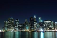 Orizzonte di New York City agli indicatori luminosi di notte Immagine Stock