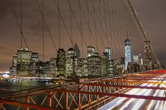 Orizzonte di notte di New York City dal ponte di Brooklyn Immagine Stock