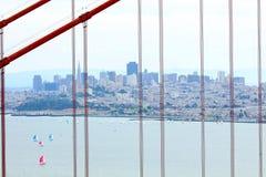 Orizzonte di San Francisco osservato attraverso i cavi di golden gate bridge Fotografia Stock Libera da Diritti