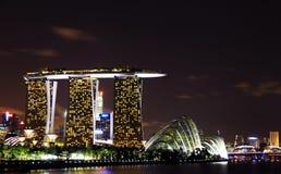 Orizzonte di Singapore di notte alle sabbie della baia del porticciolo Immagine Stock