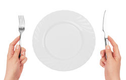 Ork with a knife in hands. Fork with a knife in hands in front of an empty plate royalty free stock images