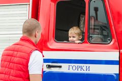 ORKI, ΛΕΥΚΟΡΩΣΊΑ - 25 ΙΟΥΛΊΟΥ 2018: Το αγόρι κάθεται σε μια κόκκινη υπηρεσία 112 διάσωσης αυτοκινήτων σε διακοπές στο πάρκο μια θ στοκ εικόνες