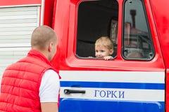 ORKI, WIT-RUSLAND - JULI 25, 2018: De jongen zit in de rode dienst 112 van de autoredding op een vakantie in het park op een de z stock foto
