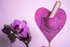 Orkidé- och polymerhjärta arkivbild