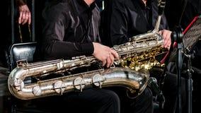 Orkiestry w czerni ubraniach siedzą na krzesłach Barytonowy saksofon na muzyka ` s podołku zdjęcia royalty free