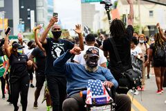 Orlando, FL, USA - JUNE 19, 2020: Wheelchair Man with American Flag. Veterans. Protests in the USA.