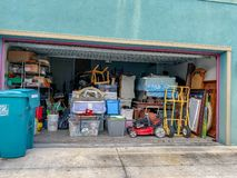 An unorganized garage filled with a lot of stuff in a neighborhood