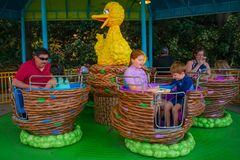 Parent and Kids enjoying Big Bird`s Twirl `N` Whirl attraction at Seaworld in International Drive area  1. Orlando, Florida. April 7, 2019. Parent and Kids royalty free stock photography