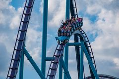 People having fun amazing Mako rollercoaster on lightblue cloudy sky background at  Seaworld 1. Orlando, Florida. April 26, 2019. People having fun amazing Mako stock photo