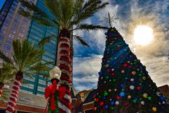 Palm trees decorated for Christmas and Christmas Tree on sunset background in Orlando Downtown area . Orlando, Florida . December 24, 2018. Palm trees decorated royalty free stock photos