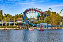 At Seaworld Panoramic view of roller coaster and flamingo boat ride on blue lake in International Drive area stock image