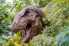 ORLANDO, FLORIDA, EUA - EM DEZEMBRO DE 2018: O dinossauro entre os arbustos com sua boca abre mostrar seus dentes no parque temát imagens de stock