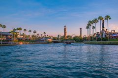 Scenic summer sunset view of City Walk pier,  with palms, plane, boat and Adventure Island lighthouse at Universal Studios area 3. Orlando, Florida. May 21, 2019 stock photo