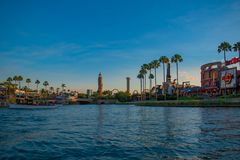 Scenic summer sunset view of City Walk pier,  with palms, plane, boat and Adventure Island lighthouse at Universal Studios area 1. Orlando, Florida. May 21, 2019 royalty free stock photos