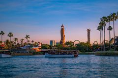 Scenic summer sunset view of City Walk pier,  with palms, plane, boat and Adventure Island lighthouse at Universal Studios area 2. Orlando, Florida. May 21, 2019 stock photos