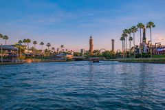 Scenic summer sunset view of City Walk pier,  with palms, plane, boat and Adventure Island lighthouse at Universal Studios area 3. Orlando, Florida. May 21, 2019 royalty free stock photography