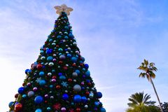 Beautiful decorated Christmas Tree and Palms Trees on cloudy lightblue sky background in International Drive area. Orlando, Florida; November 24, 2018 stock photos