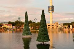 Christmas trees reflected in the lake and sky tower on sunset background in International Drive area. Orlando, Florida. November 21, 2018 Christmas trees royalty free stock image