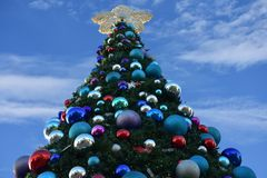 Decorated Christmas tree lightblue cloudy background in International Drive area. Orlando, Florida. November 17, 2018. Decorated Christmas tree lightblue cloudy stock image