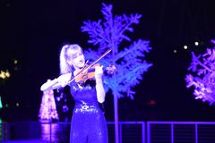 Woman artist playing violin on Christmas background in International Drive area. Orlando, Florida. November 17, 2018. Woman artist playing violin on Christmas stock photos